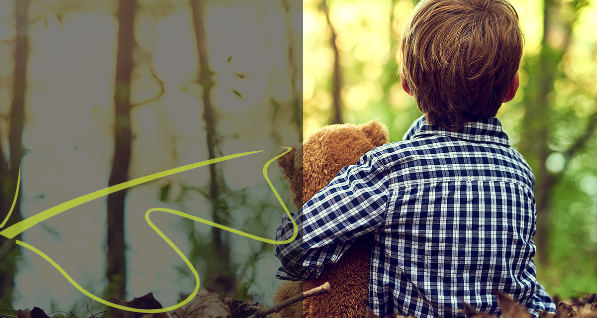 child playing in woodland with teddy bear